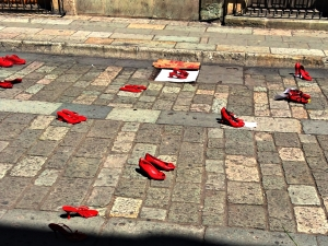 Empty red shoes cry out from the pavement.